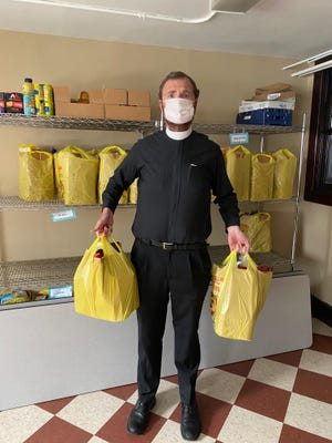 Rev. Matthew Newcomb prepares bags of food to be handed out to those in need at St. Mary's Church in Port Jervis.