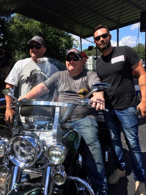 Navy veteran Michael McKinney, center, checks out the 2002 Harley-Davidson Heritage Softail he was awarded Sunday while surrounded by George Fernandez, left, brother of late Ocala police officer Don Snow, whose family donated the cycle, and Jason White, director of the local Birdwell Foundation for PTSD, at Warhorse Harley-Davidson as part of the Warrior Wheels Project on Sunday.