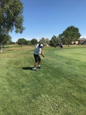 South High School's Gianni Croasdell chips onto the 15th green at Desert Hawk Golf Course last Monday during the Cyclone Invitational Golf Tournament.