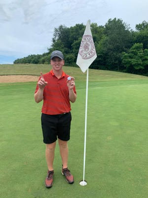 Luke Riggenbach stands next to the flag on the eighth hole at Pekin Country Club after shooting his first hole-in-one.