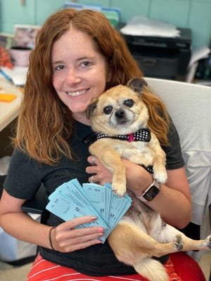 A Harbor Humane team member poses with a dog and raffle tickets during the organization's online Ales for Tails event.