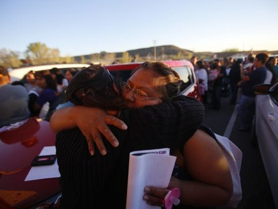 Residents embrace at a vigil for Ashlynne Mike on Tuesday