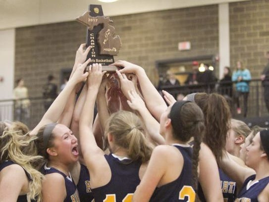 The Hartland girls basketball team celebrates its district
