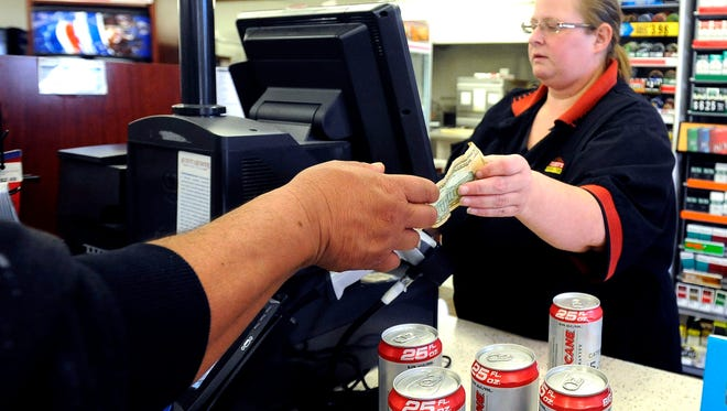 Teresa Sobiech gives change to a customer for his single-serve beer at Casey's General Store  in Sioux Falls, SD; Monday, Oct. 19, 2015. Sioux Falls City Council is talking about a single-serve booze ban.