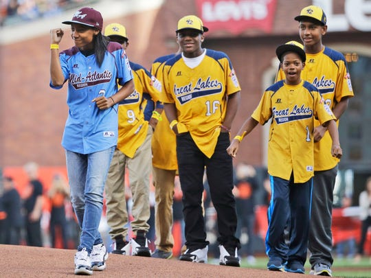 FILE - In this Oct. 25, 2014, file photo, Mo'ne Davis, the first female pitcher in Little League World Series history to pitch a complete-game shutout, is accompanied by players from the Jackie Robison West Little League team before throwing out the ceremonial first pitch before Game 4 of baseball's World Series between the Kansas City Royals and the San Francisco Giants in San Francisco. Davis broke one barrier after another when she helped her inner-city team get within one victory of the U.S. championship in the Little League World Series. (AP Photo/Matt Slocum, File)