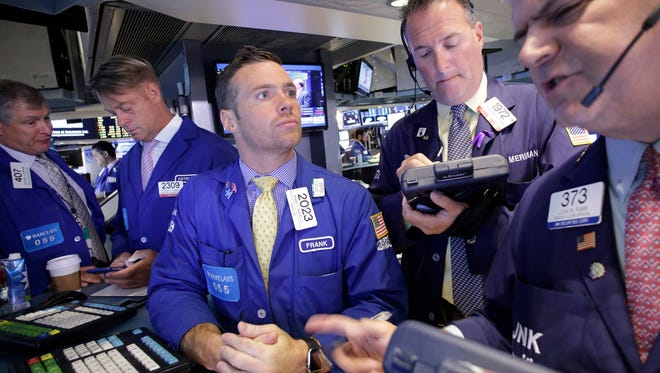 Traders Frank Masiello, center, and John Panin, right, talk about stock prices at the  New York Stock Exchange, Tuesday, July 14, 2015. (AP Photo/Mark Lennihan)