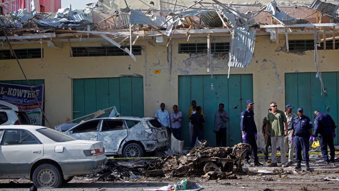 Somali soldiers stand near the wreckage of a car bomb in Mogadishu, Somalia, on Dec. 19, 2015.