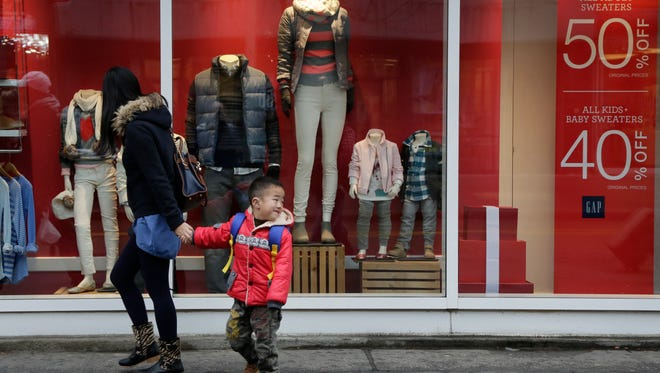 A mother and son pass a Gap clothing store window that has a notice for discount prices, Nov. 12, 2015 in the Brooklyn borough of New York.