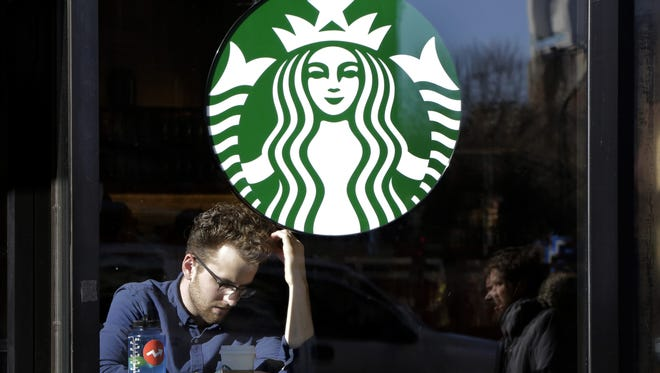 FILE - In this Jan. 11, 2016, photo, a man sits inside a Starbucks, in New York. Starbucks is changing the terms of its rewards program so that people who just get a regular cup of coffee will have to spend significantly more to earn a freebie. The Seattle-based coffee chain says its loyalty program will award stars based on the dollars spent starting in April. Currently, people earn a star for each transaction and get a free food or item of their choice after earning 12 stars. (AP Photo/Mark Lennihan)