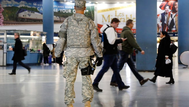 A member of the New York National Guard patrols Penn Station, Tuesday, March 22, 2016, in New York. Authorities are increasing security throughout New York City following explosions at the airport and subway system in Brussels. (AP Photo/Mark Lennihan)
