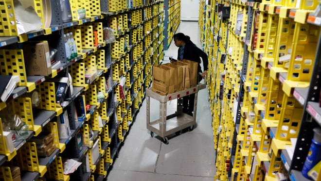 Amazon Prime employee Alicia Jackson hunts for items at the company's urban fulfillment facility in New York on Dec. 22, 2015.