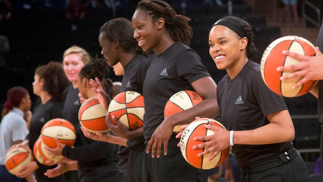 In this Wednesday, July 13, 2016 file photo, members of the New York Liberty basketball team await the start of a game against the Atlanta Dream, in New York. The WNBA has fined the New York Liberty, Phoenix Mercury and Indiana Fever and their players for wearing plain black warm-up shirts in the wake of recent shootings by and against police officers. All three teams were fined $5,000 and each player was fined $500. While the shirts were the Adidas brand - the official outfitter of the league - WNBA rules state that uniforms may not be altered in any way. (AP Photo/Mark Lennihan, File)