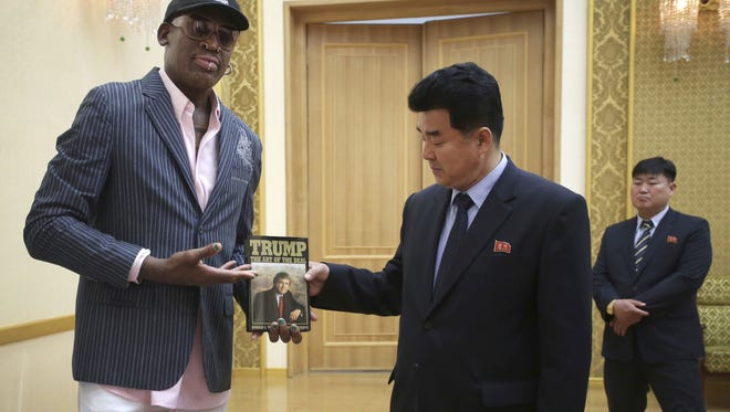 """Former NBA basketball star Dennis Rodman presents a book titled """"Trump The Art of the Deal"""" to North Korea's Sports Minister Kim Il Guk during a visit to Pyongyang on June 15, 2017."""