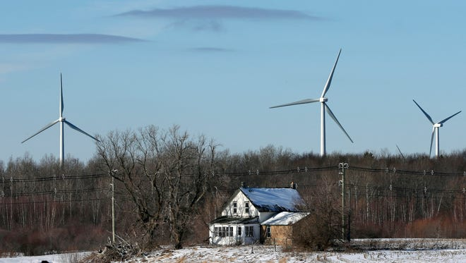 In this Jan. 15, 2017 photo, large energy producing wind turbines in the Noble Ellenburg Windpark tower above a farmhouse in Ellenburg, N.Y. State officials said new and future investments in renewable energy projects, similar to the wind turbine project, will help compensate for the loss of power generation with the closure of the Indian Point nuclear power plant.