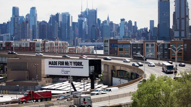 """Traffic spirals up and down a section of Route 495 to the Lincoln Tunnel, Thursday, June 21, 2018, in Weehauken, N.J. An estimated two-and-a-half-year rehabilitation project on a separate section of 495 will create """"severe congestion"""" according to the state's Department of Transportation. The New York City skyline is in the background."""