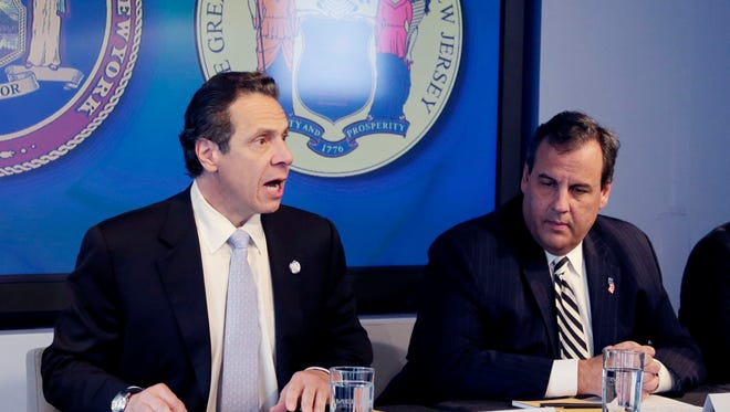 """New York Gov. Andrew Cuomo, left, speaks as New Jersey Gov. Chris Christie listens at a news conference in which they announced a mandatory quarantine for people returning to the United States from Ebola-stricken countries through airports in New York and New Jersey who are deemed """"high risk."""""""