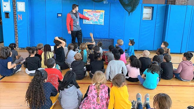 "PE teacher Ryan Koval teaches a class with students who have been using pedometers to ""Walk Across America"" and learn about the states on the way to California."