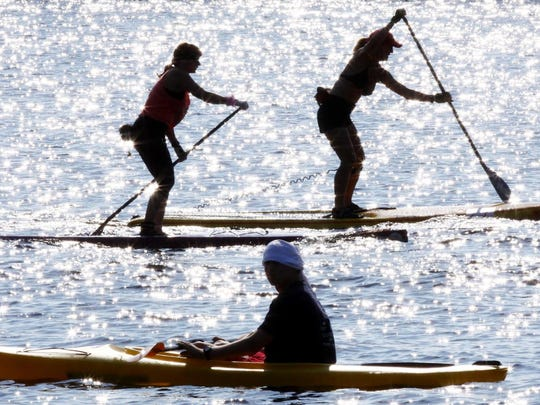 A kayaker and paddle boarders are silhouetted by the glare of the sun during the New Jersey State Paddling Championships on the Toms River Sunday, September 8, 2013 in Toms River, NJ. jody Somers / For The Asbury Park Press