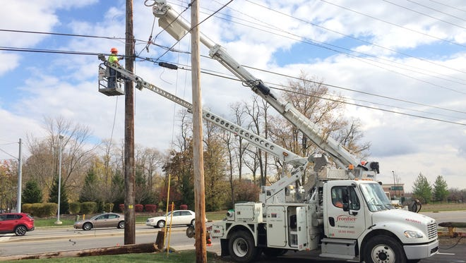 A Frontier Communications crew works on lines along Chester Boulevard at the scene of a Thursday morning accident that snapped a utility pole.