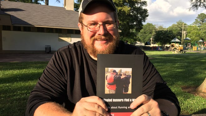 Parkway coach Kent Falting displays his new book, Motivated Runners Find a Way.