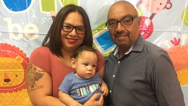 JoAnn and Raymond Medrano Jr. hold their son, Raymond Medrano III, on Sunday during his first birthday party.