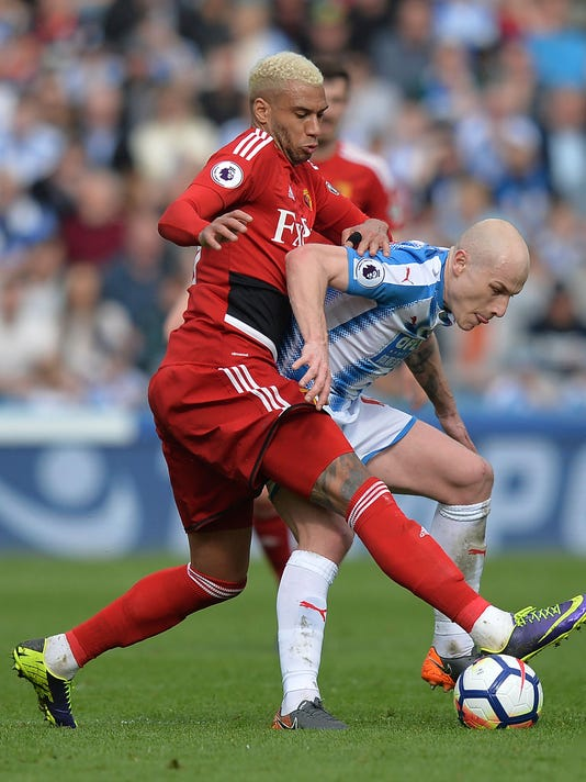 Watford's Etienne Capoue, left, competes with Huddersfield Town's Aaron Mooy for the ball during the English Premier League soccer match between Huddersfield Twon and Watfor at the John Smith's Stadium, Huddersfield, England, Saturday April 14, 2018.(Dave Howarth/PA via AP)