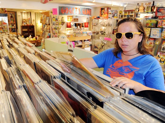 """Customer Jodi Lynn Cohee of Rehoboth Beach looks at a Talking Heads album while shopping at Gidget's Gadgets Retro Emporium """" a business on Rehoboth Avenue in Rehoboth Beach."""