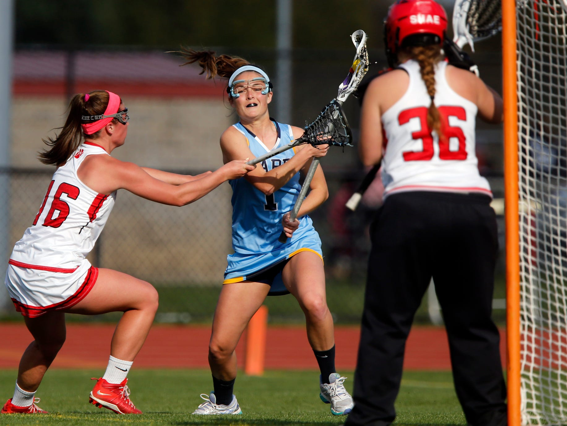 Cape Henlopen's Lizzie Frederick (center), the Delaware girls lacrosse Co-Player of the Year, battles between Polytech defender Jamie Trabaudo (left) and goalie Shae Stephan.