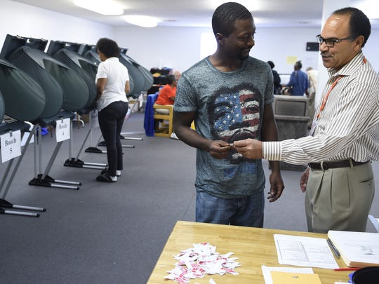 Election worker Charles Thompson, right, gives a sticker to Danyell Weaver after completing a ballot during the final day of early voting Thursday, Nov. 3, 2016, at The Love Kitchen.