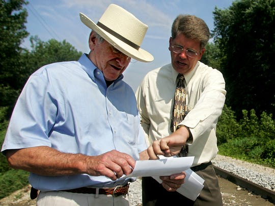 Coralville City Administrator Kelly Hayworth, right, uses a photograph to describe damage to part of the CRANDIC railway that was caused by flooding to former Sen. Tom Harkin during a tour of some of the damaged parts of the city on Monday, Aug. 4, 2008.