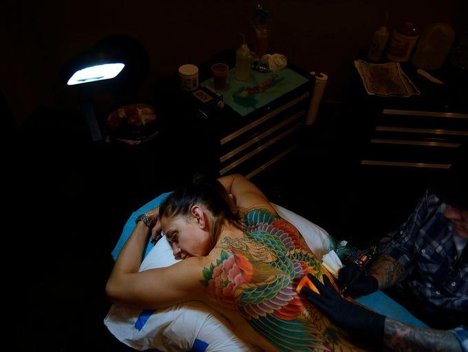 Tattoo artist Paul Dhuey works on Jessica Newman, 42,