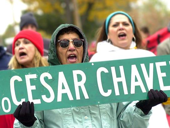 Margarita Noyola holds a Cesar Chavez Avenue sign as