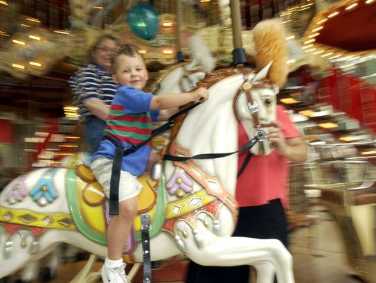 A young child rides the carousel at the Danbury Fair