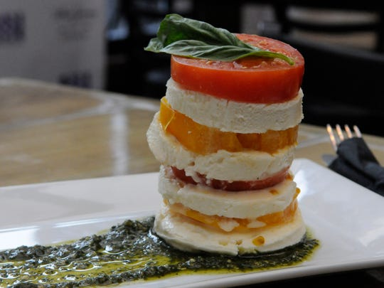 On Olivella's Antipasti menu, La Torre di Caprese stacks mozzarella di buffalo, red and yellow local tomatoes, pesto, basil and Sicilian oregano, photographed on Wednesday, March 15, 2017.