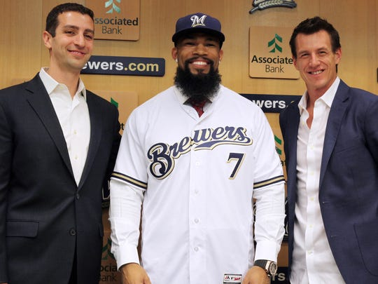 GM David Stearns (left) and manager Craig Counsell (right) pose with their new first baseman, Eric Thames, at a news conference Tuesday at Miller Park.