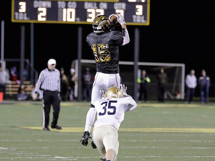 Avon WR Andrew Griffin goes high for a catch in front of Cathedral's Kyle Hoeper Friday night.