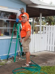 Home Depot volunteers Juan Lopez, on ladder, and Ron