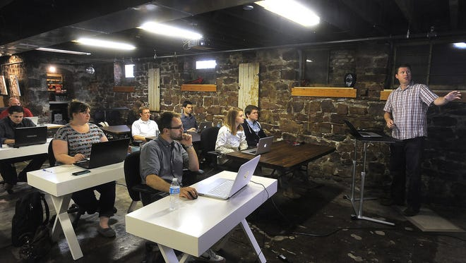 Josh Stroschein (right) instructs during Code Bootcamp, a course in web development, in the Rock Island Building in downtown Sioux Falls.