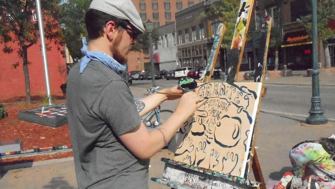 An artist demonstrates during a 2014 Art Crawl.