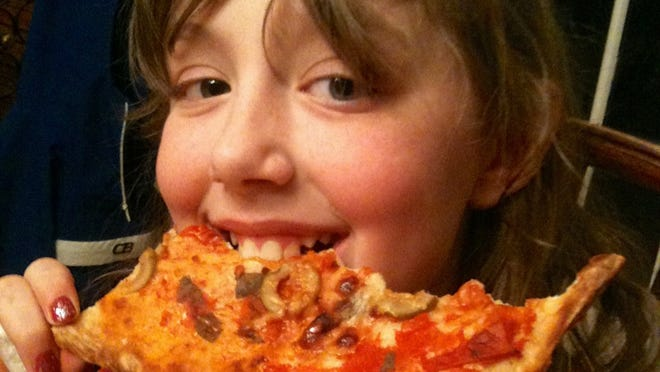 Greta Schaub, 13, takes a bite out of vegetable pizza made with no-sugar tomato sauce during her family's year of no added sugar.