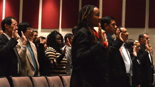 Newly-naturalized citizens take the oath of allegiance at Liberty Tech High School on Monday morning.