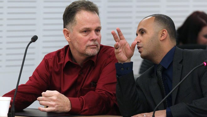 """Charles """"Chase"""" Merritt, center, who is charged in the deaths of a family of four whose bodies were found three years after their disappearance, talks with private attorney, Jimmy P. Mettias, as he waits for his preliminary hearing in San Bernardio, Calif., Tuesday, May 19, 2015. The hearing was postponed Tuesday. The family's skeletal remains were discovered in a shallow grave in Victorville, Calif., nearly 100 miles north of their San Diego County home. (John Gibbins/U-T San Diego via AP)  NO SALES; COMMERCIAL INTERNET OUT; MANDATORY CREDIT"""