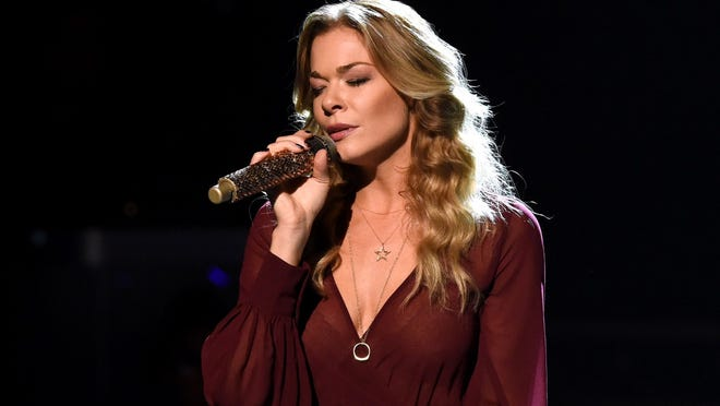 """LeAnn Rimes is receiving criticism, but also much support, after an Instagram post that showed her getting a tattoo that says """"god's work."""" Some told Rimes """"God"""" should be capitalized."""