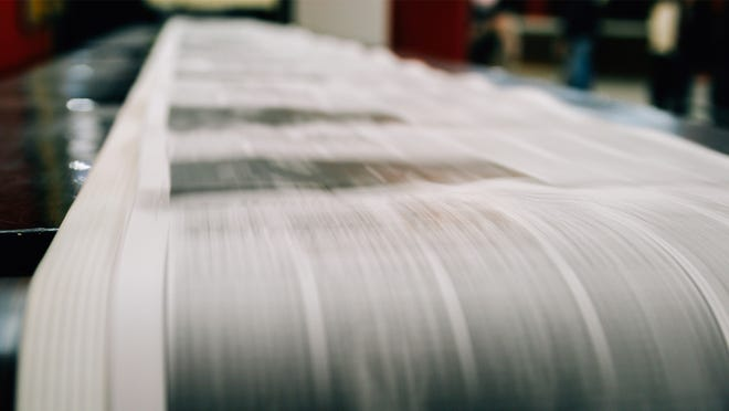 Printing press shoots off newspaper.