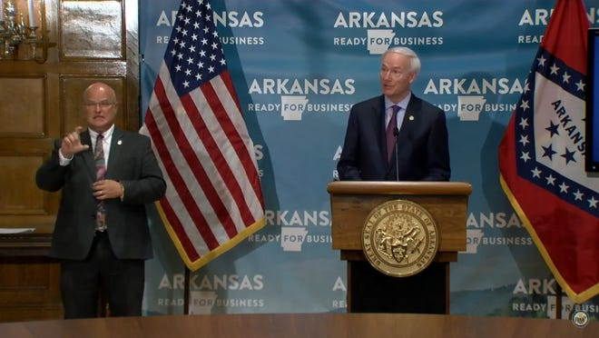 Gov. Asa Hutchinson speaks to reporters in the State Capitol on Wednesday.