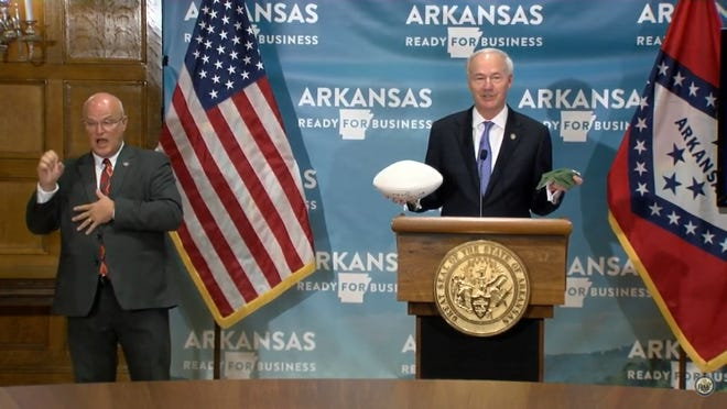 Gov. Asa Hutchinson used props to explain that wearing a mask is key to the return of contact sports.