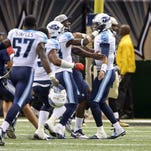 Tennessee Titans quarterback Marcus Mariota (8) is mobbed by teammates after his touchdown pass in overtime defeated the New Orleans Saints 34-28 at the Mercedes-Benz Superdome.
