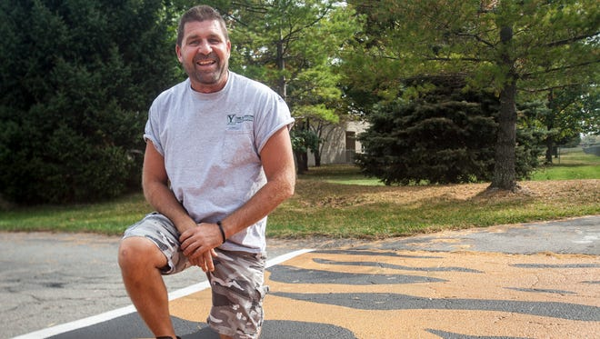 Mike Cantanzarite kneels at the crosswalk he painted with tiger stripes at South Tiger Drive and West River Road in front of Pleasant View Elementary.