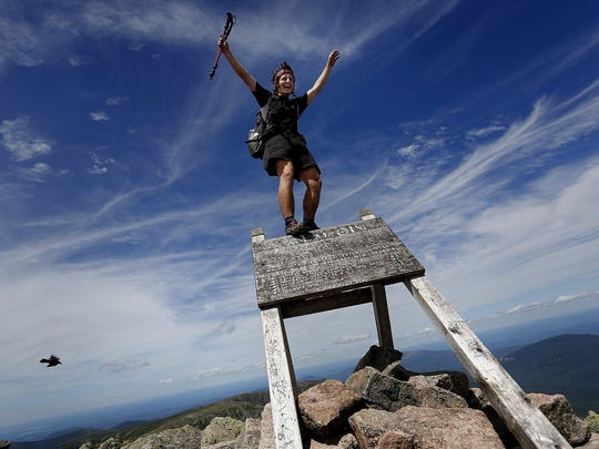 """FILE - In this July 19, 2015 file photo, Jesse Metzler, 19, of Newton, Ma., who goes by the trail name """"Sputnik,"""" celebrates on the top of a sign marking the northern terminus of the Appalachian Trail at the summit of Mt. Katahdin in Baxter State Park, Maine. Baxter officials say thru-hikers are openly using drugs and drinking alcohol, camping where they aren?t supposed to and trying to pass their pets off as service dogs. Jensen Bissell, director of the park, says the trail may need to end somewhere besides Katahdin if something doesn?t change soon. (Derek Davis, Portland Press Herald via AP, File)"""