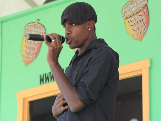Deante Ramon sings as he and other local singers perform as they compete during the final round of the West Side Nut Club voice contest on the main stage during the Fall Festival in Evansville in 2012.